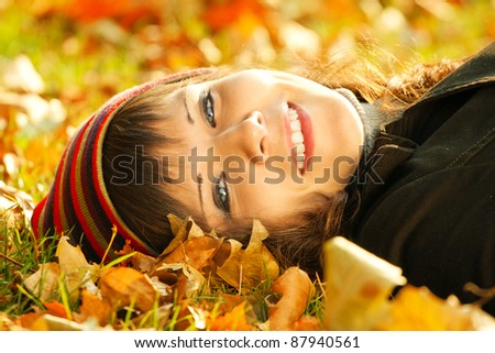 Beautiful woman enjoy autumn in park. Lying, laughs and looks at the camera. Portrait of smile teenage girl.