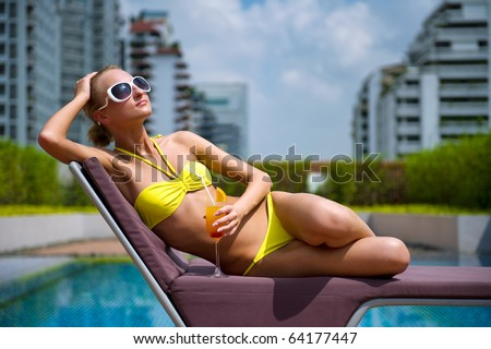 Beautiful woman enjoying a cocktail in the pool - stock photo
