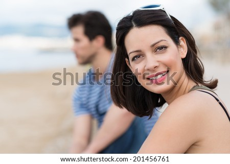 Beautiful woman enjoying a day at the beach turning to smile at the camera with a blurred man visible behind - stock photo