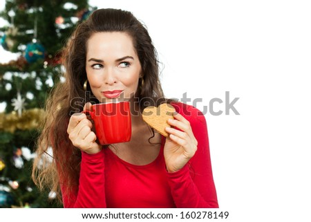 Beautiful woman enjoying a hot drink and gingerbread cookie in front of a Christmas tree. Isolated on white. - stock photo