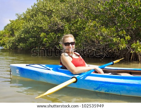 Beautiful woman enjoying a kayak ride - stock photo