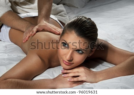 Beautiful woman enjoying a massage on bed - stock photo