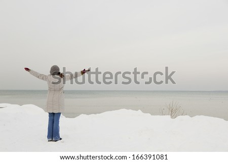 Beautiful woman enjoying a winter day full of snow - stock photo