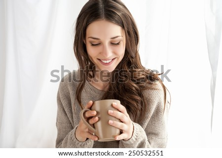 beautiful woman enjoying coffee in the morning sitting by the window - stock photo