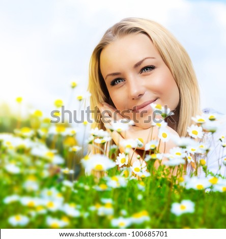 Beautiful woman enjoying daisy field and blue sky, nice female lying down in the meadow of flowers, pretty girl relaxing outdoor, happy young lady and green spring nature in harmony - stock photo