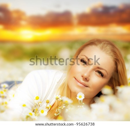 Beautiful woman enjoying daisy field at sunset, nice female lying down in the meadow of flowers, pretty girl relaxing outdoor, happy young lady and spring nature in harmony