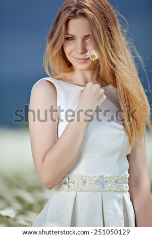 Beautiful woman enjoying daisy field, nice female lying down in meadow of flowers, pretty girl relaxing outdoor, having fun, holding plant, happy young lady and spring green nature, harmony concept - stock photo