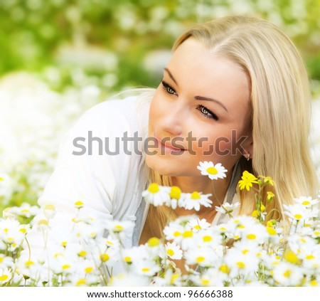 Beautiful woman enjoying daisy field, nice female lying down in the meadow of flowers, pretty girl relaxing outdoor, having fun, happy young lady and spring green nature, harmony & freedom concept - stock photo
