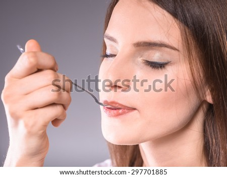 Beautiful woman enjoying dessert with closed eyes over gray background. - stock photo