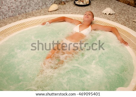 Beautiful woman enjoying in Jacuzzi at the spa center.