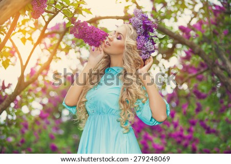 Beautiful woman enjoying lilac garden, young woman with flowers in green park. cheerful teenager walking outdoor. soft light style color - stock photo