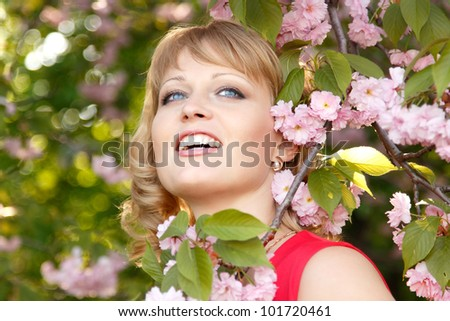Beautiful woman enjoying near blooming Japanese cherry tree. Spring outdoor