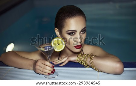 beautiful woman enjoying near the pool her vacation with a glasses of martini. beautiful and perfect makeup, clean skin, jewelry on the body. - stock photo