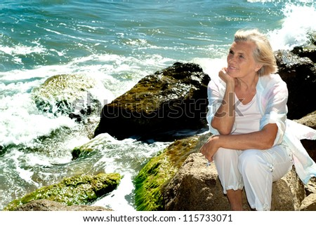 Beautiful woman enjoying the sea breeze with herself - stock photo