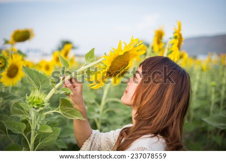 Beautiful woman enjoys blooming sunflower in the sunflowers field - stock photo