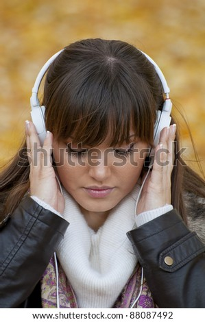 Beautiful woman enjoys listening music in headphones - stock photo