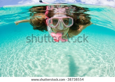 beautiful woman enjoys snorkeling in tropic waters - stock photo