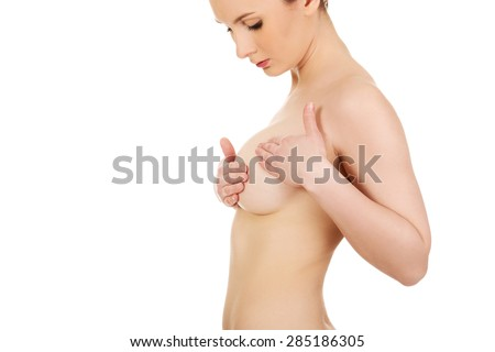 Beautiful woman examining her breast. - stock photo