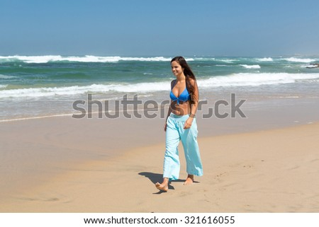 Beautiful woman exercising at the beach - fitness concept - stock photo