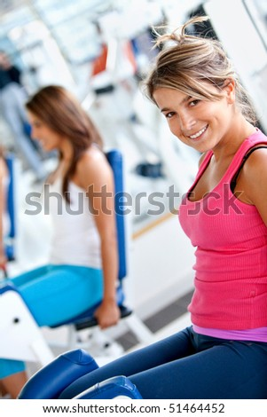 Beautiful woman exercising at the gym on machines