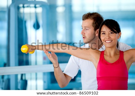 Beautiful woman exercising at the gym with her trainer - stock photo