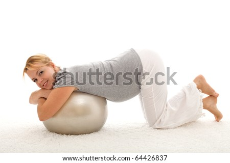 Beautiful woman exercising with large ball kneeling on the floor indoors - isolated - stock photo