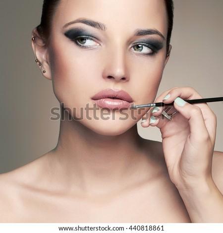 Beautiful woman face. beauty girl with Perfect make-up.Makeup artist applies lipstick - stock photo