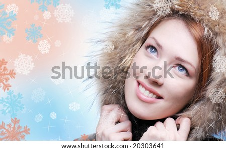 Beautiful  woman face close-up covered head by winter hood.