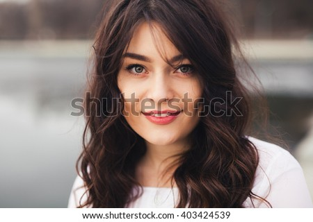 Beautiful woman face closeup. Close up portrait of young woman with natural make up smiling and looking to camera outdoors. - stock photo