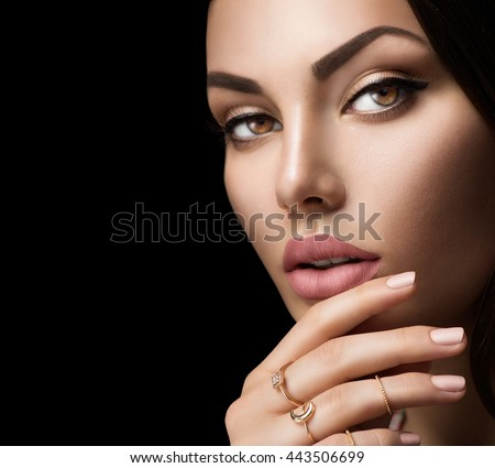 Beautiful woman face portrait isolated on black background. Sexy lips with fashion natural beige matte lipstick makeup, beige nails, trendy midi rings on her fingers. Closeup - stock photo