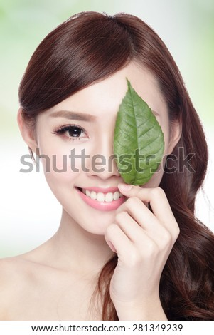 beautiful woman face portrait with green leaf , concept for skin care or organic cosmetics , asian beauty
