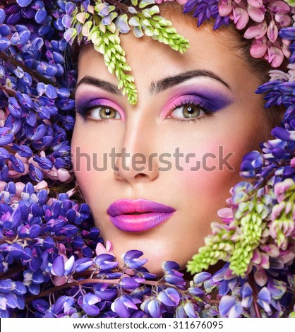 Beautiful woman face surrounded by violet flowers. Spring Flower. Springtime. Professional makeup, - stock photo