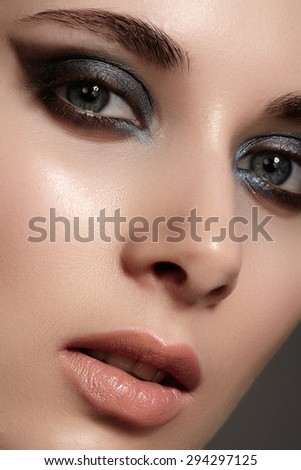 Beautiful woman face with bright make up eye with sexy liner makeup. Fashion big arrow shape on woman's eyelid. Chic evening make-up, healthy face - stock photo