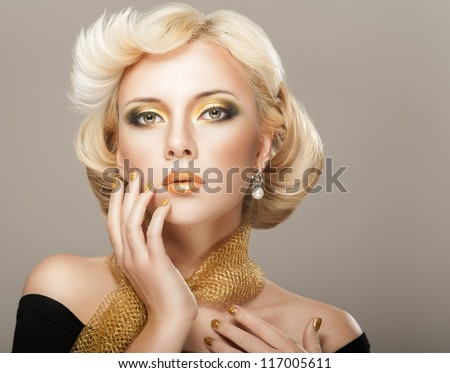Beautiful woman face with luxury gold makeup