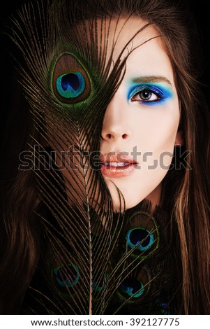 Beautiful Woman. Face with Makeup and Peacock Feather - stock photo