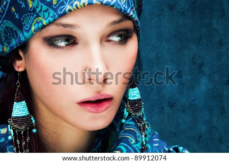 beautiful woman face with oriental scarf around, studio shot