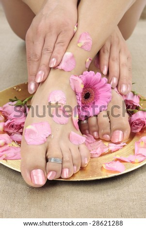 Beautiful woman  feet with flowers and petals closeup - stock photo