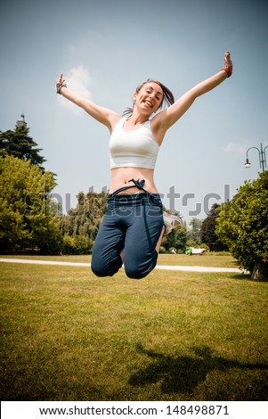 beautiful woman fitness jumping at the park - stock photo