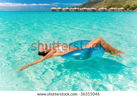 beautiful woman floating in turquoise waters near tropical resort - stock photo
