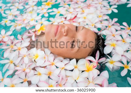 beautiful woman floating with plumeria flowers