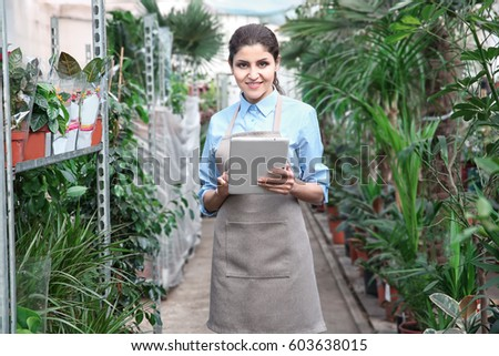 Beautiful woman florist with tablet at greenhouse