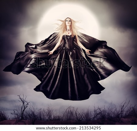Beautiful woman - flying halloween witch in midnight outdoor about full moon with black developing cloak - stock photo