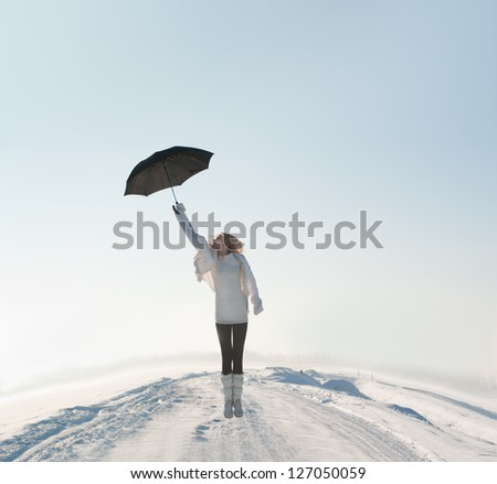 beautiful woman flying with umbrella on road in winter - stock photo