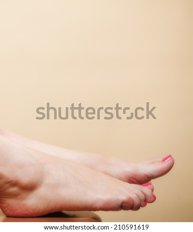 Beautiful woman foot body care pedicure on orange background - stock photo