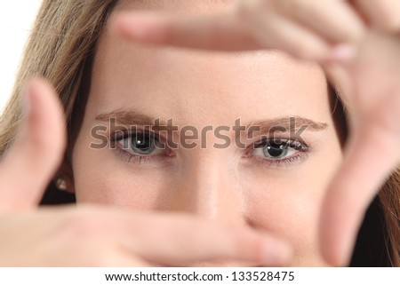 Beautiful woman framing her blue eyes with the fingers on a white isolated background - stock photo