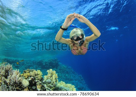 Beautiful woman free dives to explore a Coral reef in the Sea - stock photo