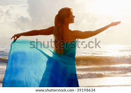 beautiful woman from behind as she has her hand outstretched as if holding the sun and looking at it in a goddess like pose. - stock photo