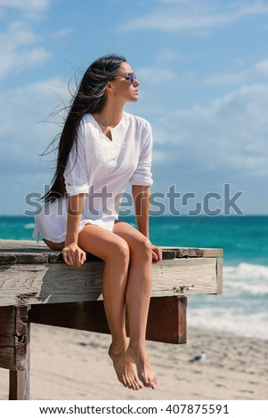 Beautiful woman full body portrait sit on a lifeguard tower. Hollywood beach in Miami, florida.  - stock photo