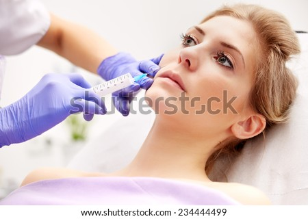 Beautiful woman gets an injection in her face
