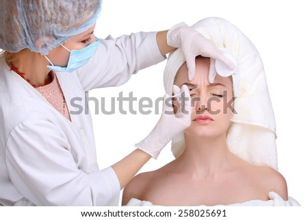 Beautiful woman gets an injection in her face - stock photo